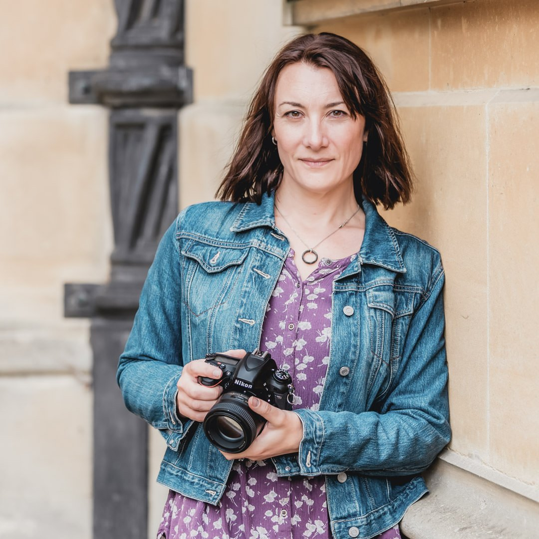 female photographer holding camera and leaning against wall