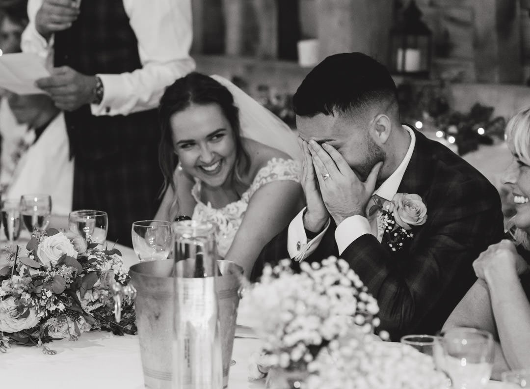 groom holding his head in his hands while the bride laughs during best man speech