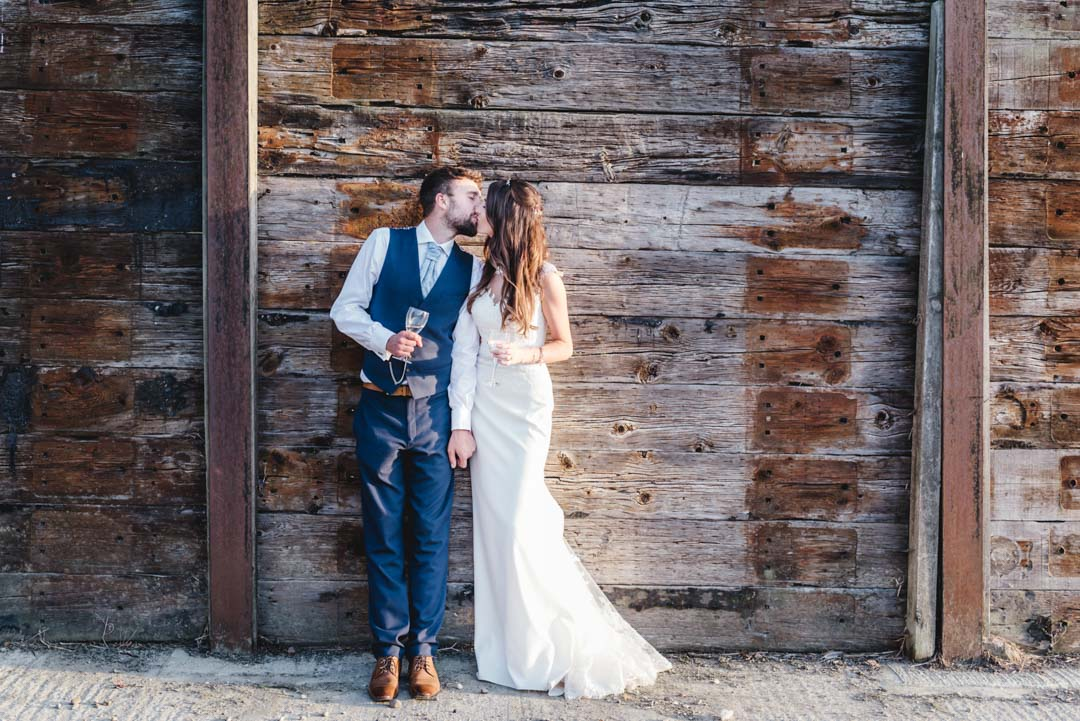 bride and groom kissing and holding chamagne glasses in the evening sun against the wall of a barn