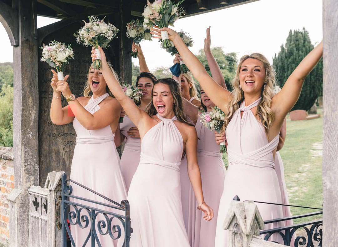 six bridesmaids waiting for the bride at the church gate laughing and waving their bouquets in the air