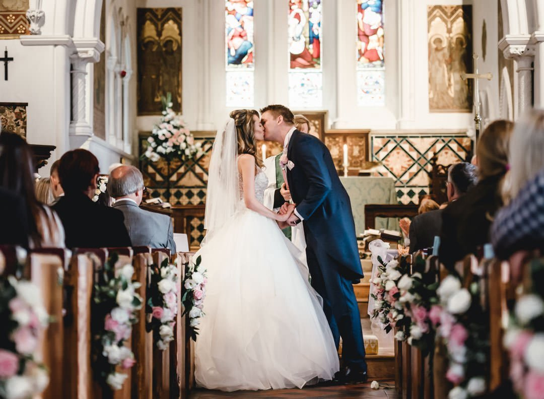 groom kissing his bride during their church wedding ceremony